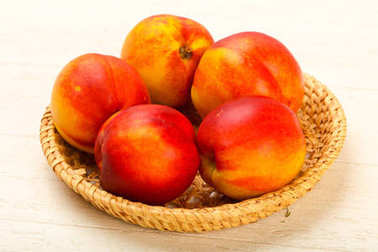 Ripe Nectarines heap over wooden background