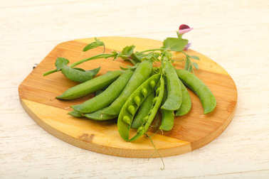 Ripe green peas with leaves over wooden background