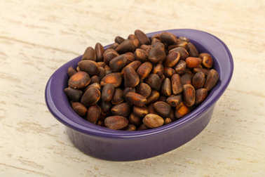 Cedar nuts heap in the bowl over wooden background