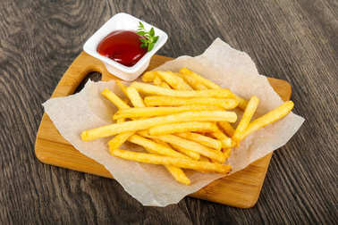 French fries with tomato ketchup over wooden background