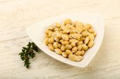 Raw White beans in the bowl over wooden background