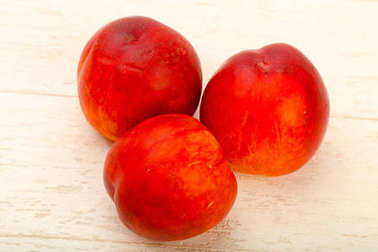 Three ripe Nectarines over wooden background