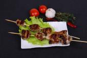 Vepřový kebab špejle v talíři s listy salátu a rajčaty
