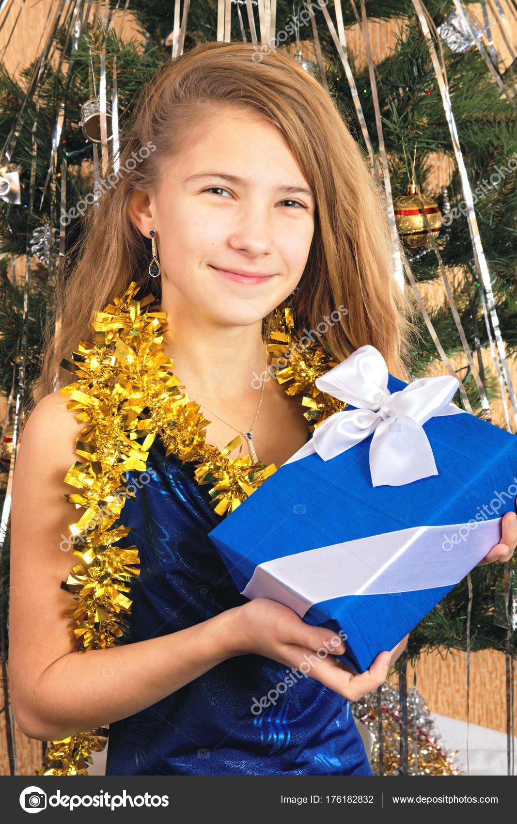 Mädchen Teenager im eleganten Kleid hält ein Weihnachtsgeschenk ...