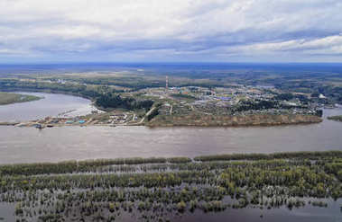Siberian village on the banks of the river in spring flood