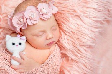 lovely newborn girl holding toy on pink fluffy blanket
