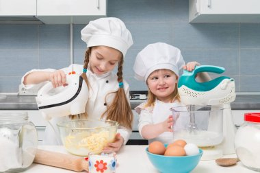 two little girls in chef uniforms