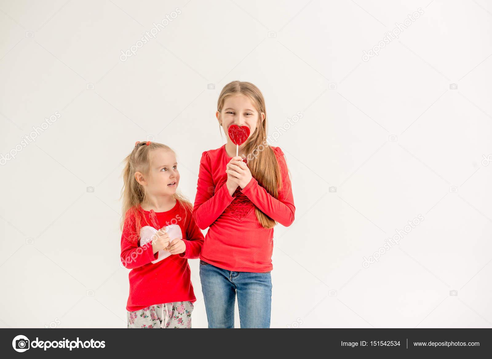 09111d32c8395 Zwei süße Schwestern mit herzförmigen Lutscher — Stockfoto © tan4ikk ...