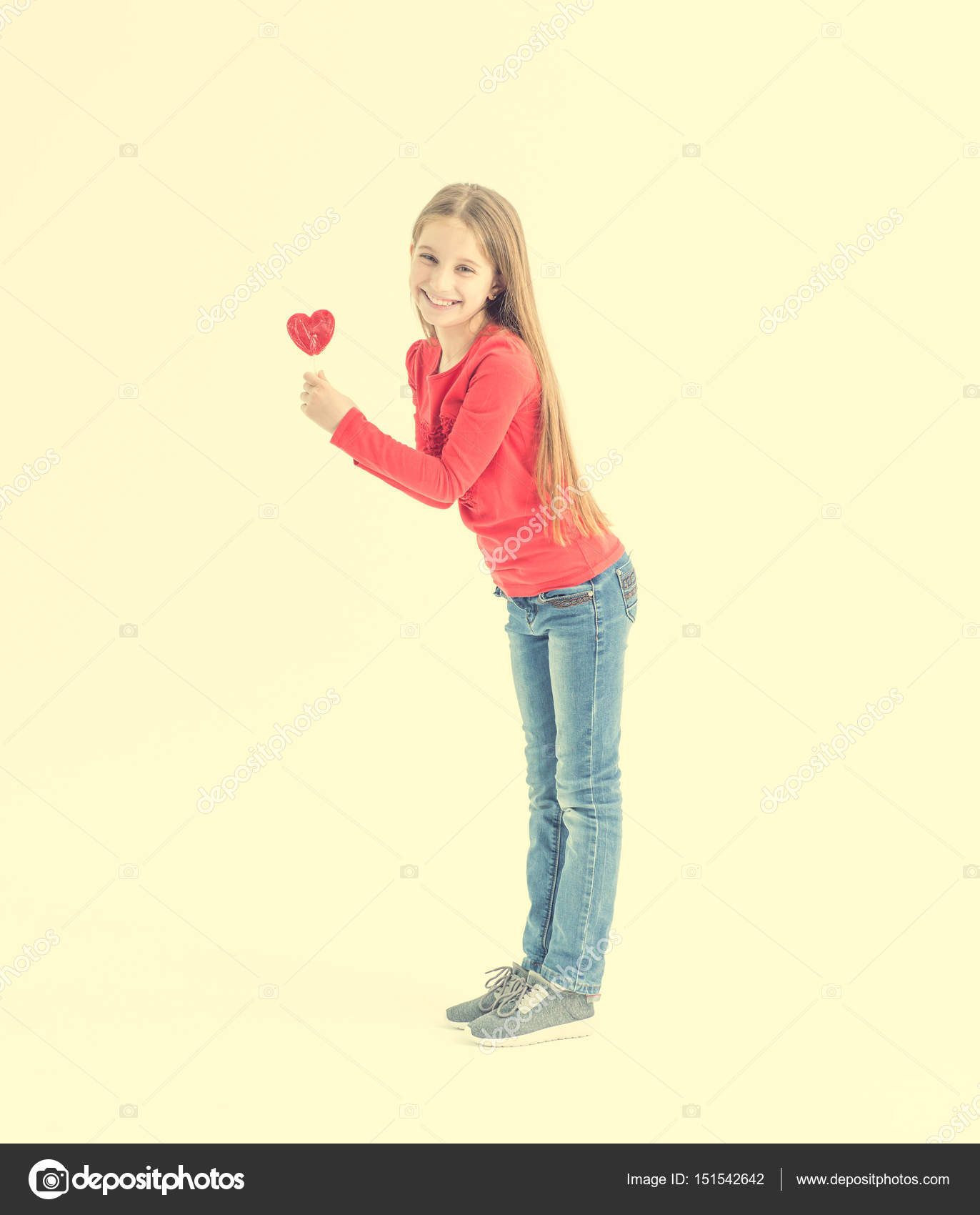 6076b348492 Εφηβικό κορίτσι σε ένα κόκκινο μπλουζάκι με σχήμα καρδιάς γλειφιτζούρια —  Εικόνα από tan4ikk