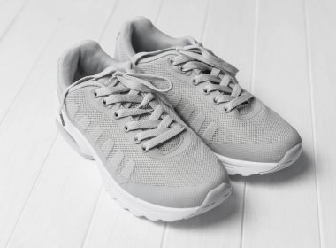 Gray cozy running shoes sitting on wood