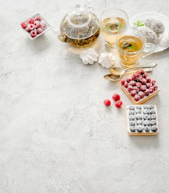 Breakfast with a variety of cakes, berries and tea. Top view. Space for text stock vector