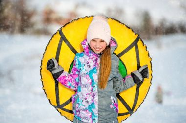Active girl holding snow tubing