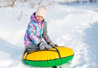 Girl with snowtube on snowy downhill