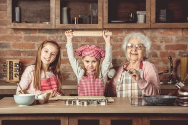 Little grandchilds ready to make cookies with grandmother