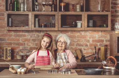 Granny with granddaughter roll out the dough