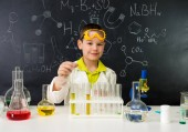 Fotografie schoolboy gown and gloves watching chemical experiment in tube