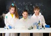 Fotografia tre bambini eccitati dopo esperimento chimico