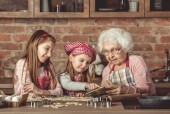 Grandma and granddaughters spreading dough