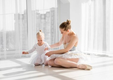 Mother cuddling with daughter sitting on the floor in dance studio