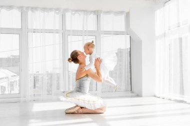 Mother in ballet outfit holding on hands small daughter