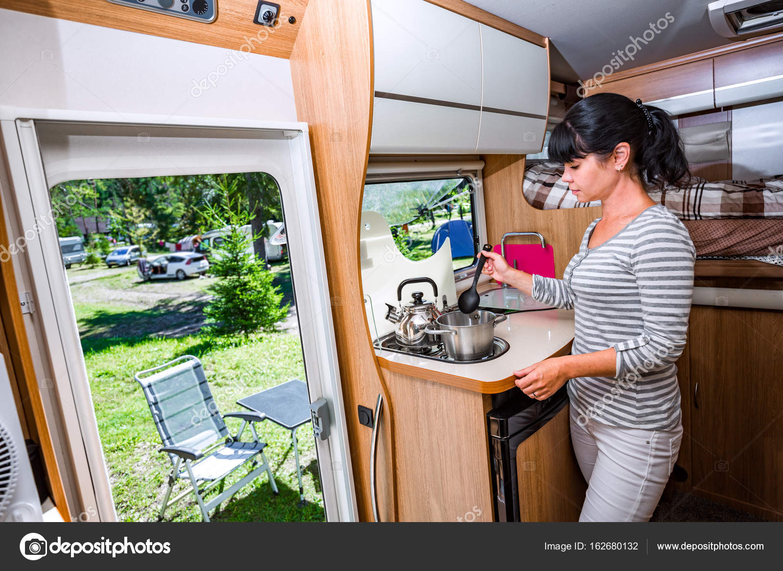 Woman cooking in camper motorhome interior stock photo for Auto interieur kuisen