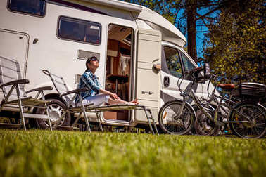 Woman resting near motorhomes in nature. Family vacation travel,