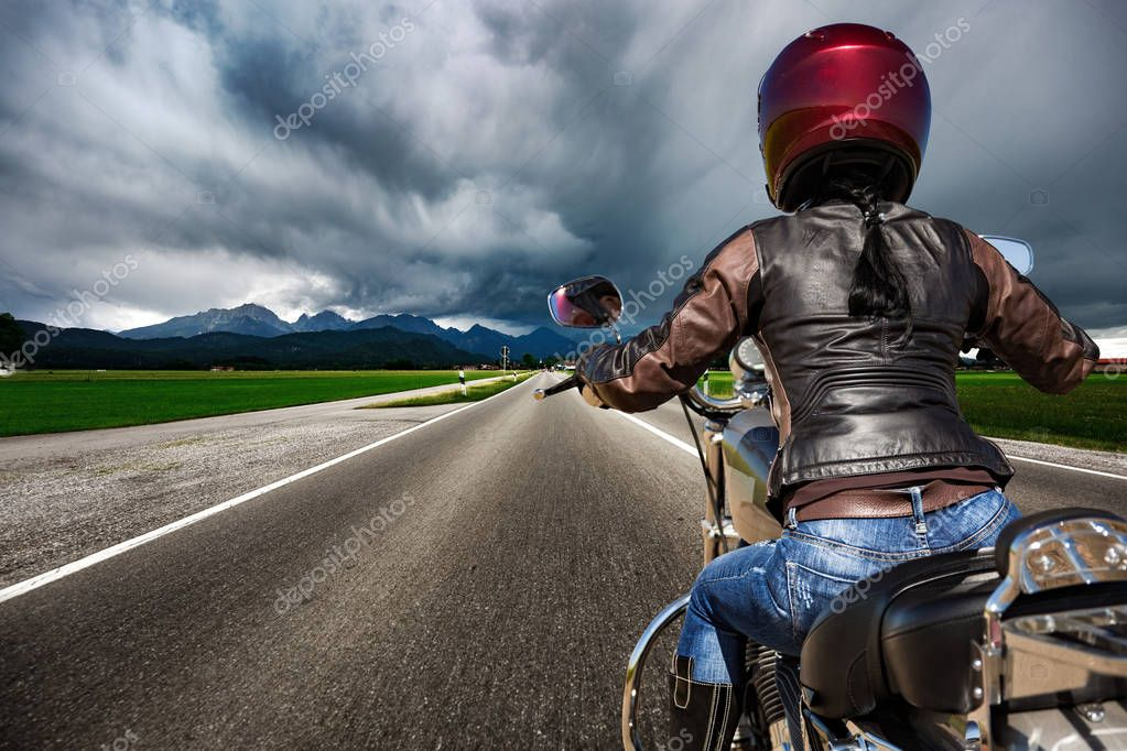 Biker girl on a motorcycle hurtling down the road in a lightning