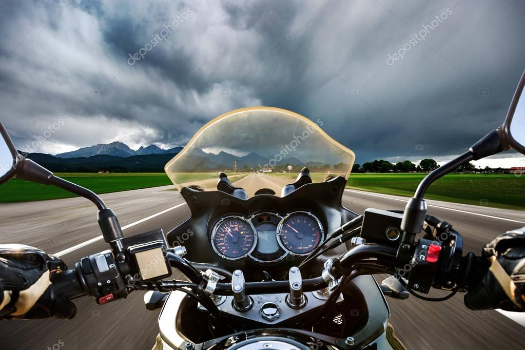 Biker on a motorcycle hurtling down the road in a lightning stor
