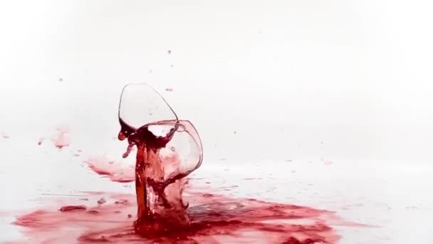 Zerbrechen des Rotweinglases in Zeitlupe auf weißem Hintergrund