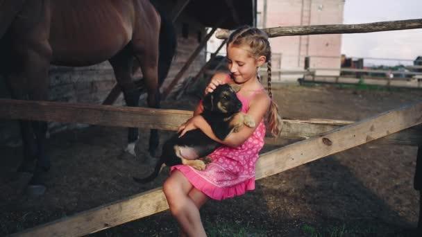 Kudrnatá dívka hladí štěně ve stáji