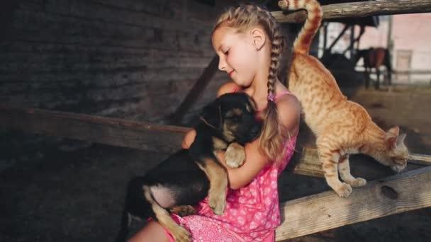 Kudrnatá dívka hladí štěně a kočka na farmě
