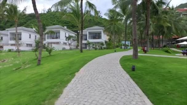 Blick auf moderne Villa, Garten mit Palmen und Rasen