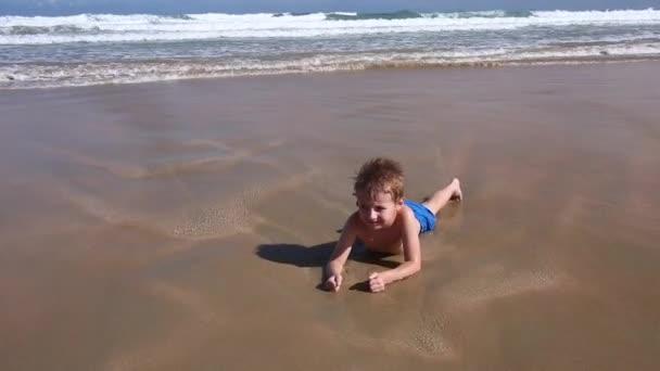 Junge spielt und hat Spaß im Wasser am Strand