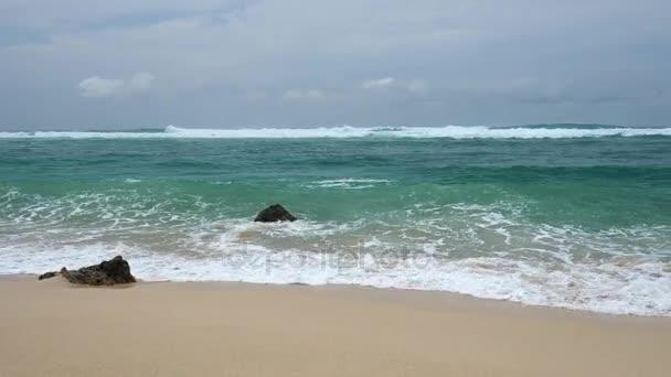 Gyönyörű vad homokos strand, a tiszta víz és a hullámok