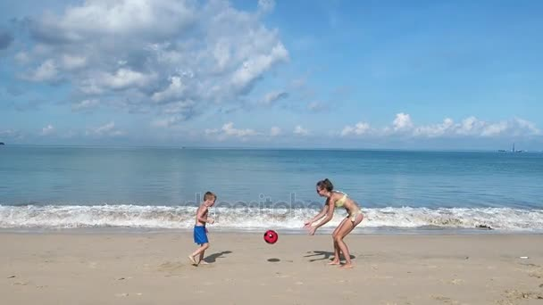 Mother and Son Having Fun and Playing With Ball on a Sandy Beach
