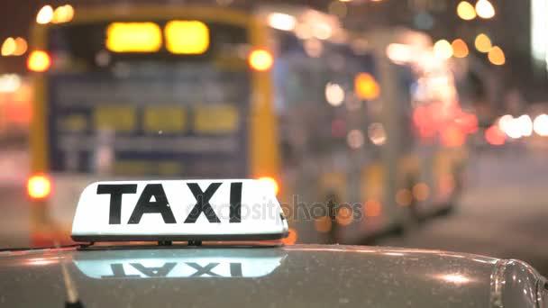 Svítící nápis Taxi proti projíždějících aut na noční ulici velkoměsta