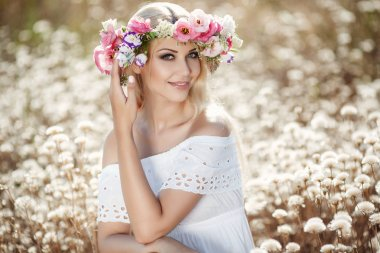 Summer portrait of a beautiful blonde woman with long straight hair,beautiful makeup and a nice smile,straight white teeth,dressed in a light white sundress,on his head wearing a wreath of colorful flowers posing outdoors in flowery field stock vector