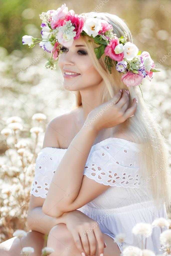 Beautiful woman with a wreath of flowers in summer field