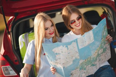 Two beautiful women are traveling on a red car