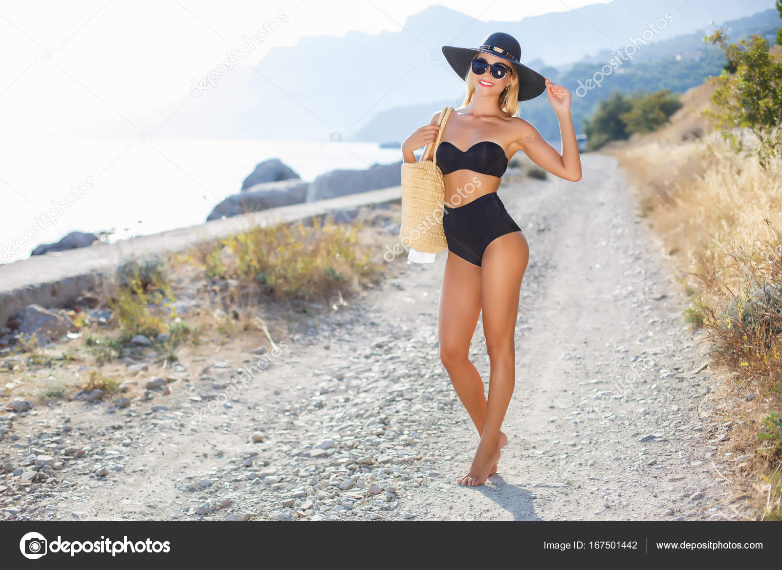 02fcbad0f7 Young beautiful woman with a slender figure, blonde in dark sun glasses and  a big black hat from the sun, black bikini, beach bag beige, posing alone  ...