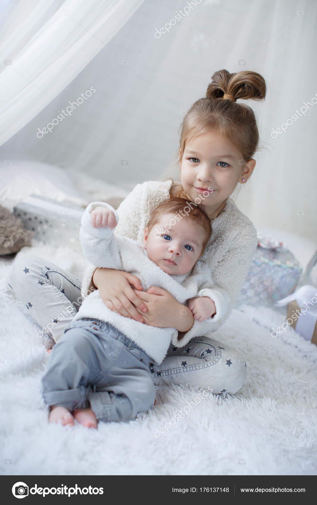 little girl embracing newborn baby brother little girl baby boy