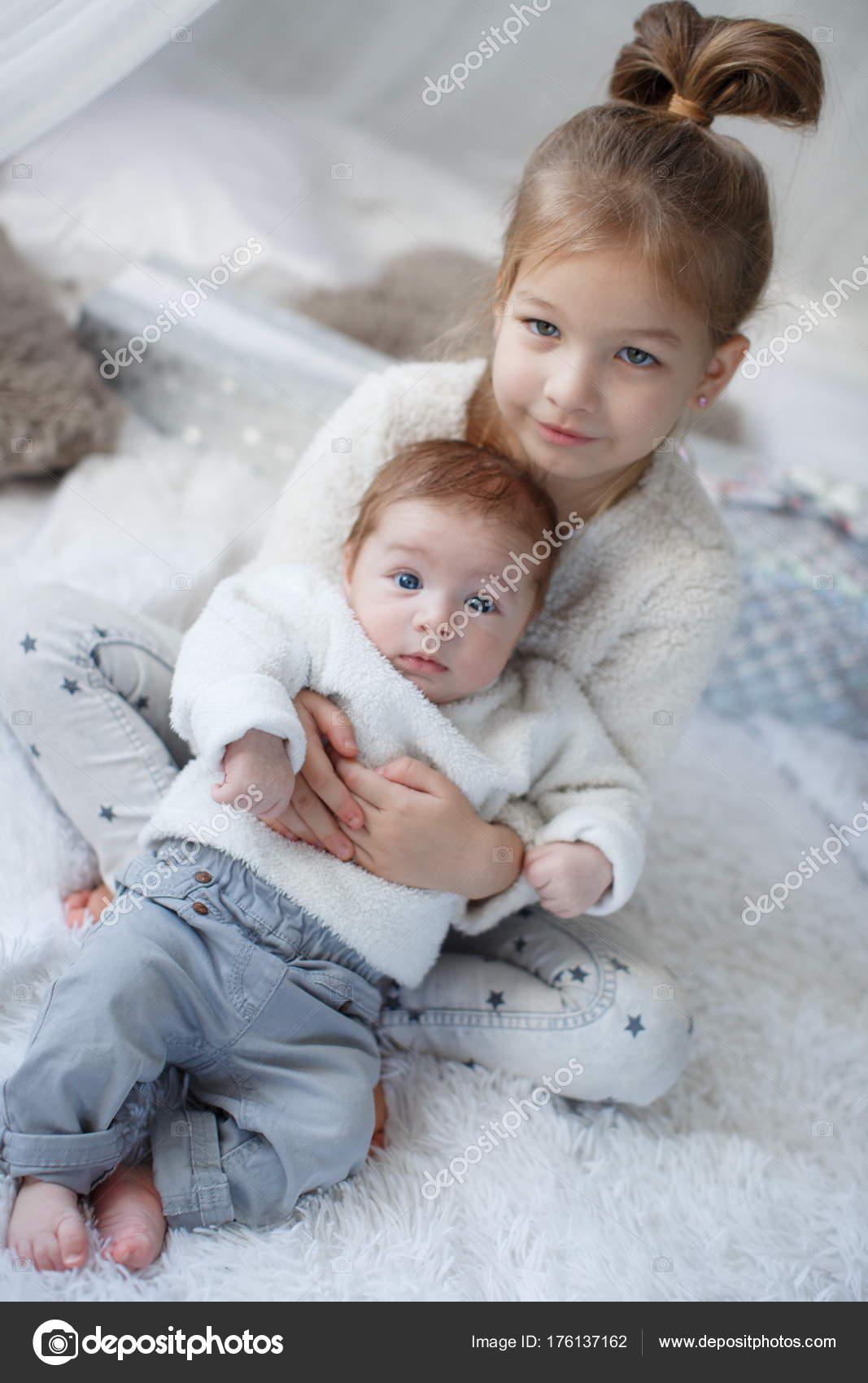 Bambina che abbraccia un fratello neonato. Ragazza e bambino ragazzo  fratello e sorella che giocano nel letto dei genitori. Ragazza carina e un  ragazzo ... 38ef9fb8420c