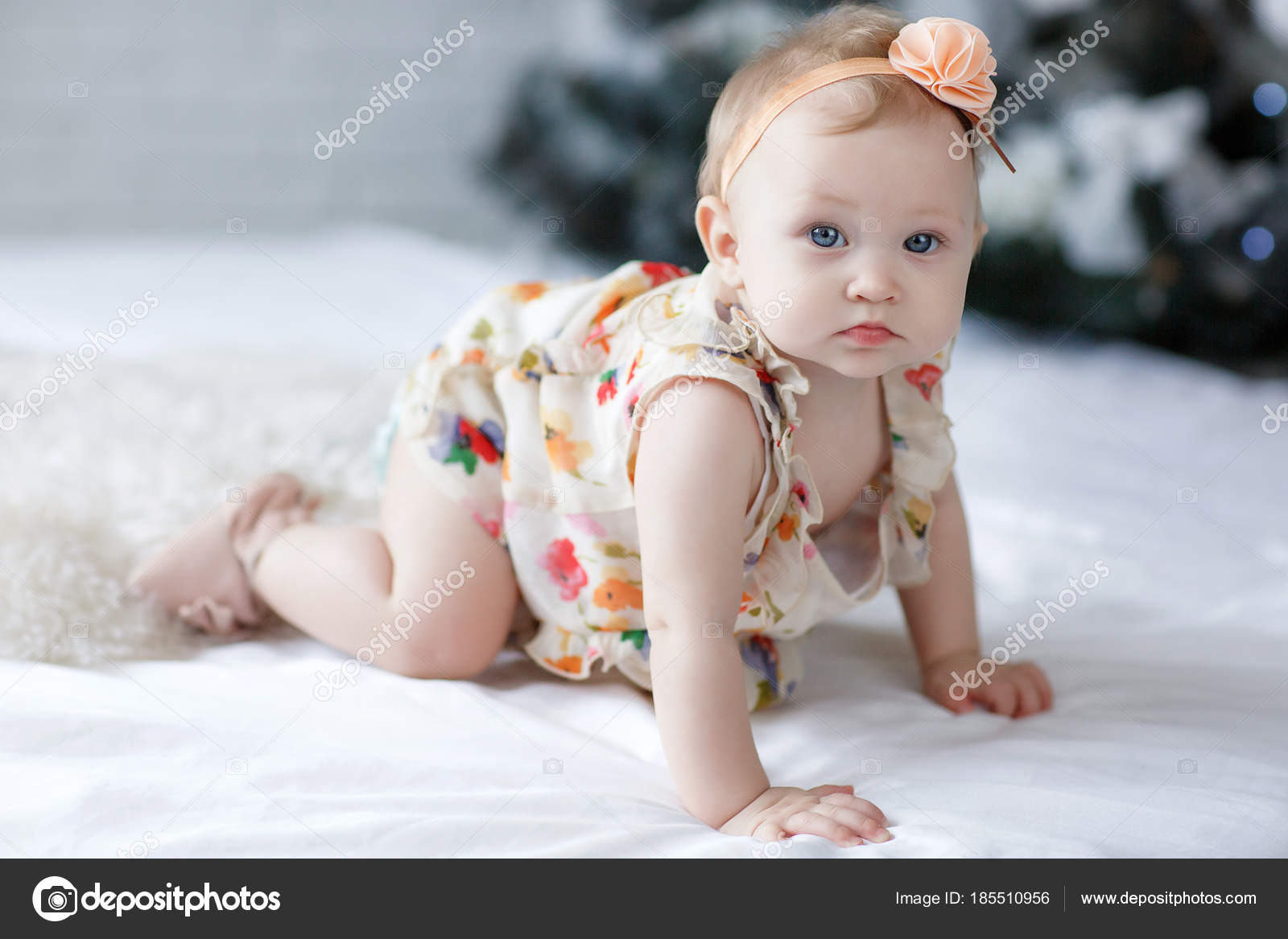 Close up of a eight nine months old baby girl with blue eyes newborn child little adorable smiling and attentive girl looking surprised at the camera
