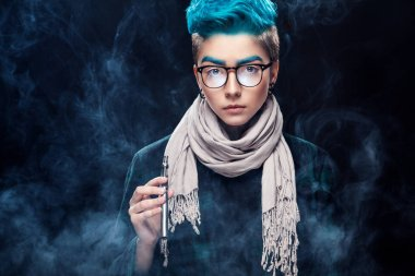 hipster woman with blue hair in glasses smoking vape on black background