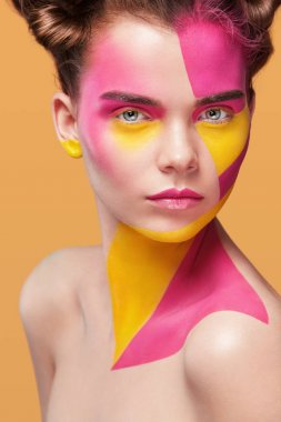 Portrait of the bright beautiful girl with art colorful painting make-up and bodyart