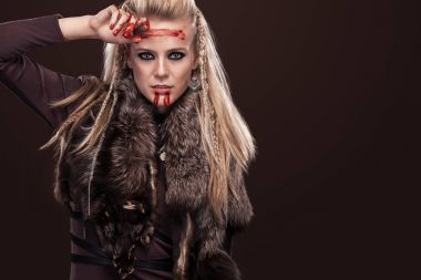 Portrait of viking woman in a traditional warrior clothes. Face in blood.