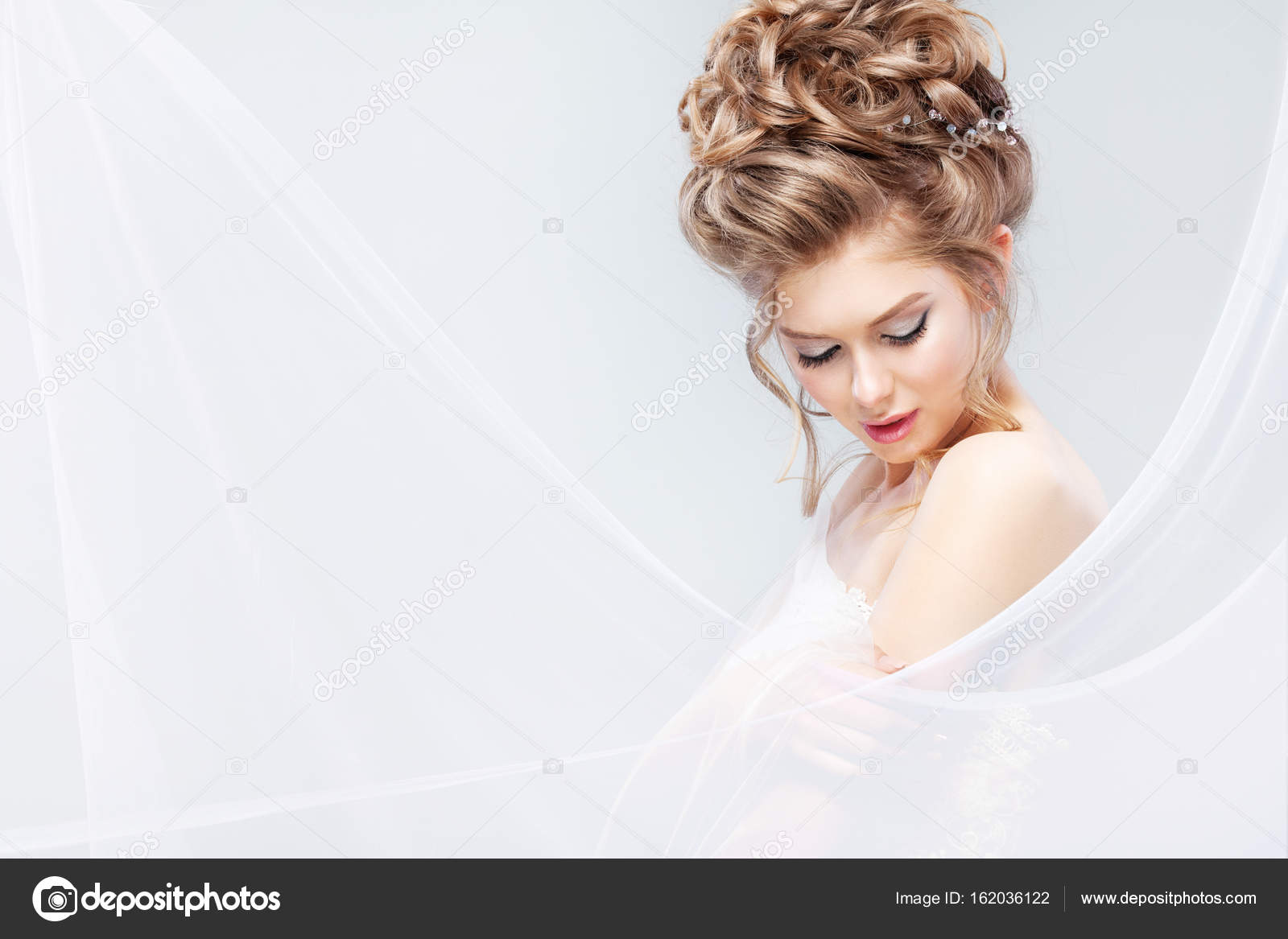 Beautiful bride with fashion wedding hairstyle - on gray background ...