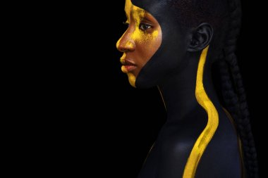 Cheerful young african woman with art fashion makeup. An amazing woman with black and yellow paint makeup