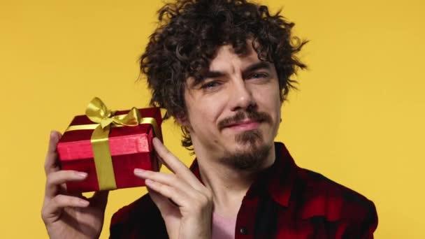 Muž dává červený dárek na Valentýna nebo Mezinárodní den žen. Narozeninové překvapení. Hezký šťastný evropský muž s vousy v košili s úsměvem izolované na žlutém pozadí.