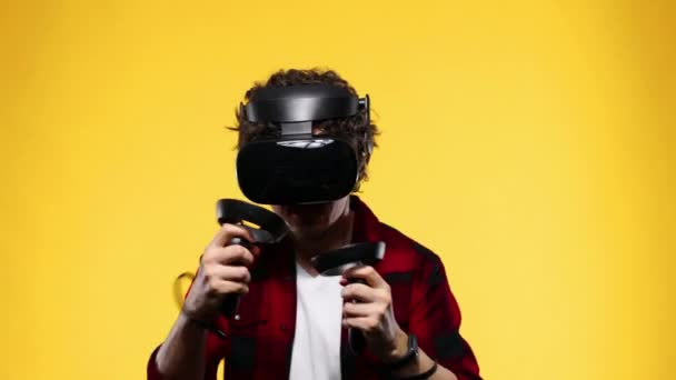 Young man with curly hair using a VR headset and experiencing virtual reality isolated on yellow background